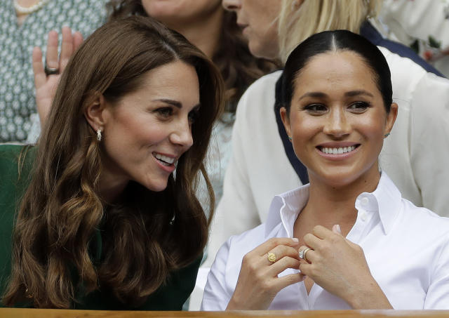FILE - In this Saturday, July 13, 2019, file photo, Kate, Duchess of Cambridge, left, and Meghan, Duchess of Sussex chat as they sit in the Royal Box on Centre Court to watch the women's singles final match between Serena Williams of the United States and Romania's Simona Halep on day twelve of the Wimbledon Tennis Championships in London. (AP Photo/Ben Curtis, File)