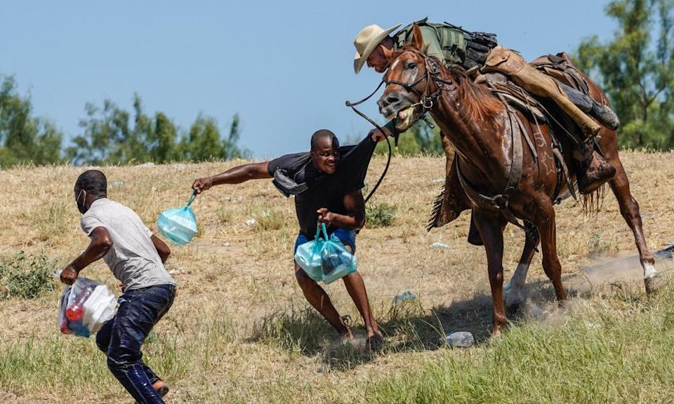 A US border patrol agent on horseback tries to stop a Haitian man from entering an encampment near the international bridge in Del Rio, Texas, on Sunday.