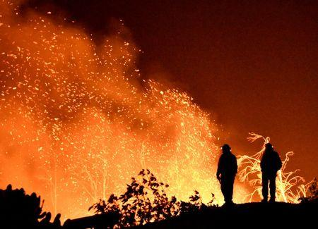 FILE PHOTO: Firefighters keep watch on the Thomas wildfire in the hills and canyons outside Montecito, California
