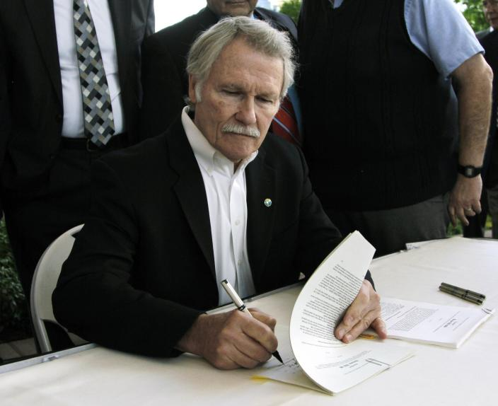 FILE - In this July 1, 2011, file photo, Oregon Gov. John Kitzhaber signs two health care bills in Portland, Ore. The Obama administration is buying into Oregon's ambitious health care initiative, announcing Thursday that it's tentatively agreed to chip in $1.9 billion over five years to help get the program off the ground.The federal government could save $1.5 trillion over the next 10 years if all 50 states adopted Oregon's approach, the governor said. (AP Photo/Don Ryan, file)