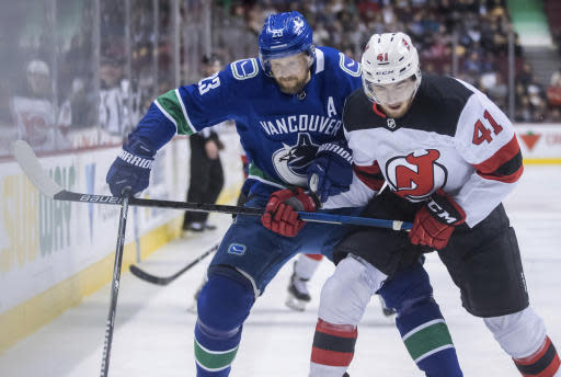 Vancouver Canucks' Alexander Edler, left, of Sweden, and New Jersey Devils' Michael McLeod vie for the puck during the first period of an NHL hockey game Friday, March 15, 2019, in Vancouver, British Columbia. (Darryl Dyck/The Canadian Press via AP)