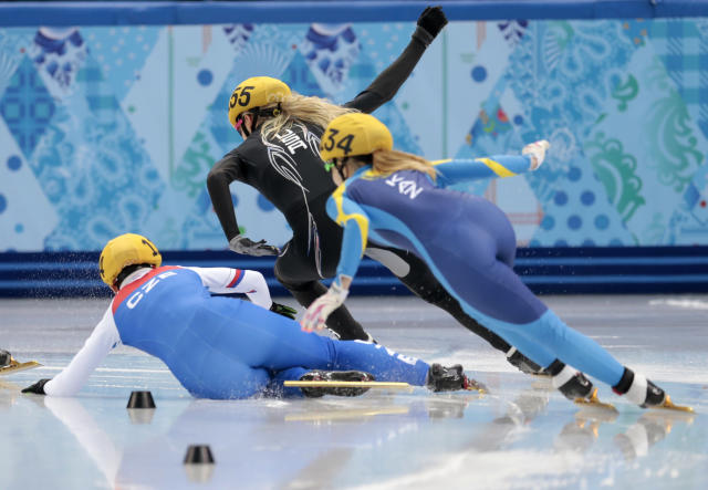Katerina Novotna of the Czech Republic, left, crashes out as she competes in a women's 1000m short track speedskating heat at the Iceberg Skating Palace during the 2014 Winter Olympics, Tuesday, Feb. 18, 2014, in Sochi, Russia. (AP Photo/Ivan Sekretarev)