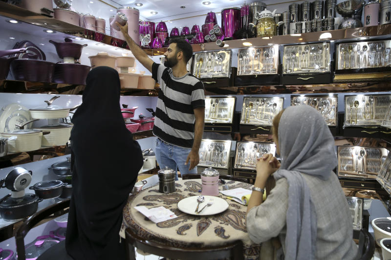 In this Thursday, Sept. 6, 2018 photo, Alireza Alihosseini, an Iranian salesclerk at a kitchenware shop, shows Chinese-made goods to customers at the Grand Bazaar, in Tehran, Iran. It's hard not to see China wherever you look in Iran. From Chinese goods flooding markets to its business people eager for deals as Western business interests flee, Iran likely will further embrace Beijing as an alternative market for its crude oil and financial transactions amid uncertainty over the nuclear deal. (AP Photo/Vahid Salemi)