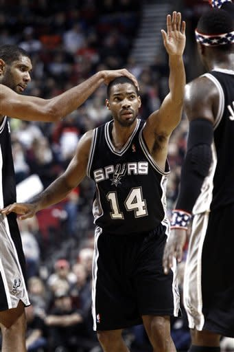 San Antonio Spurs guard Gary Neal, middle, is patted on the head by Spurs center Tim Duncan as he celebrates scoring with other teammates during the second half of their NBA basketball game against the Portland Trail Blazers in Portland, Ore., Saturday, Nov. 10, 2012. Neal came off the bench to lead the Spurs with 27 points and beat the Trail Blazers 112-109.(AP Photo/Don Ryan)