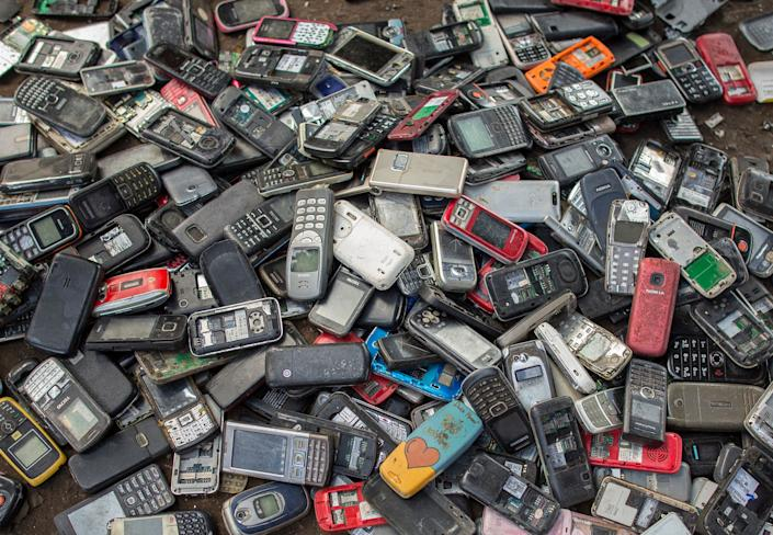 """Old mobile phones piled up at a scrapyard in Ghana's capital city, Accra. Last year, Apple alone sold <a href=""""https://www.statista.com/statistics/276306/global-apple-iphone-sales-since-fiscal-year-2007/"""" rel=""""nofollow noopener"""" target=""""_blank"""" data-ylk=""""slk:more than 217 million iPhones"""" class=""""link rapid-noclick-resp"""">more than 217 million iPhones</a>. (Photo: Thomas Imo via Getty Images)"""