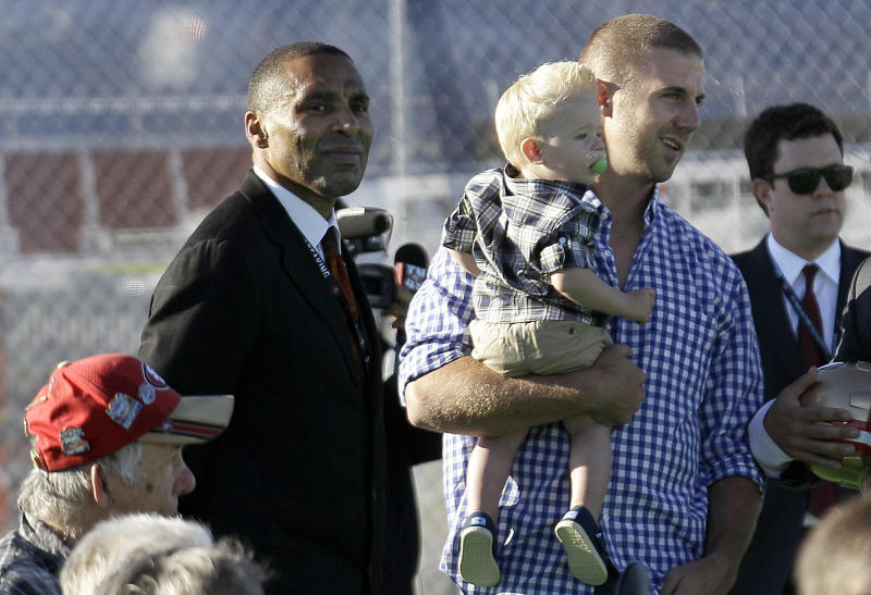 San Francisco 49ers quarterback Alex Smith, right, holds his son Hudson as he stands next to former 49ers running back Roger Craig at a groundbreaking ceremony at the construction site for the 49ers' new NFL football stadium in Santa Clara, Calif., Thursday, April 19, 2012. (AP Photo/Jeff Chiu)