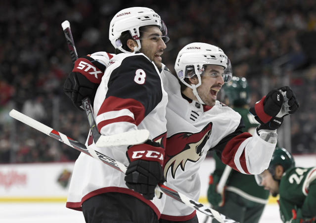 Arizona Coyotes' Nick Schmaltz (8) congratulates right wing Conor Garland on his goal against the Minnesota Wild during the second period of an NHL hockey game Thursday, Nov. 14, 2019, in St. Paul, Minn. (AP Photo/Hannah Foslien)