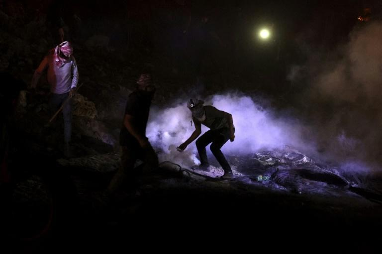 A Palestinian protester throws back a tear gas canister fired by Israeli soldiers during nighttime clashes