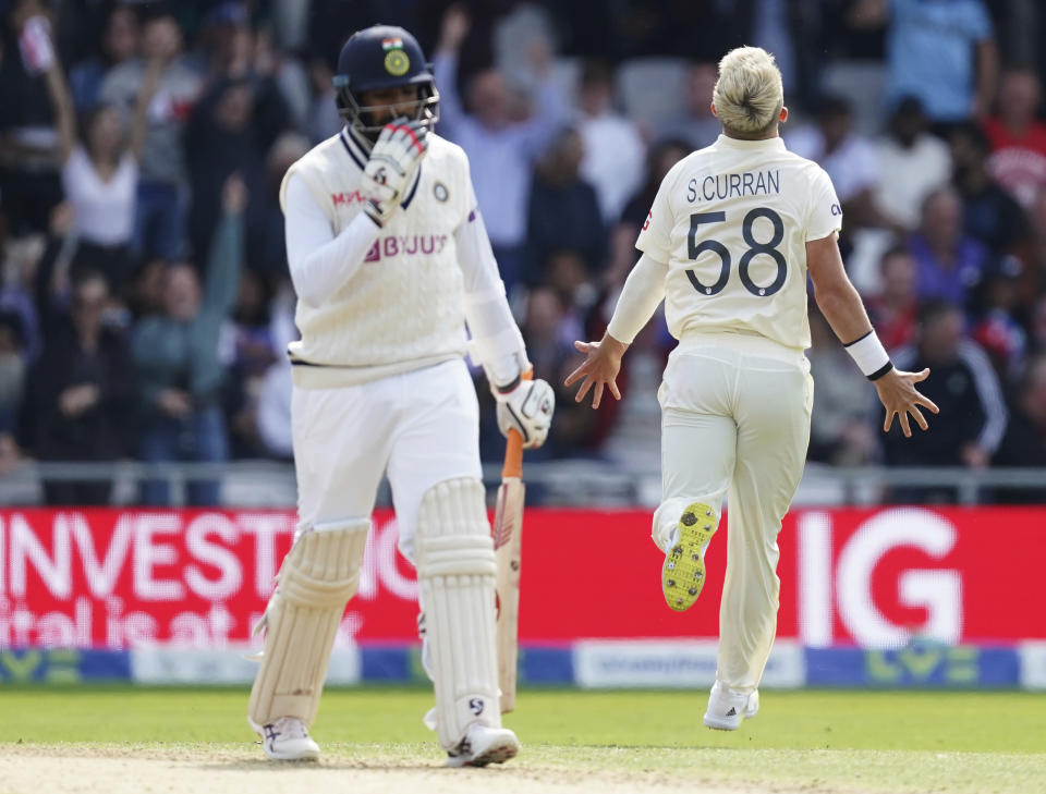 England's Sam Curran, right, celebrates the dismissal of India's Jasprit Bumrah, left, during the first day of third test cricket match between England and India, at Headingley cricket ground in Leeds, England, Wednesday, Aug. 25, 2021. (AP Photo/Jon Super)