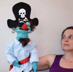 A pirate puppet who looks crochety is seen on the hand of a pupetteer.