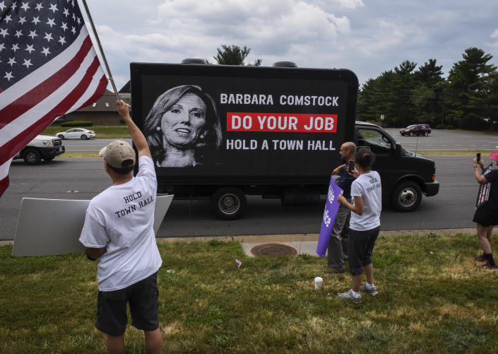 Activists cheer as a new mobile electronic billboard to help unseat Comstock passes by on Leesburg Pike on June 22, 2017 in Sterling, Va. (Photo: Bill O'Leary/The Washington Post via Getty Images)