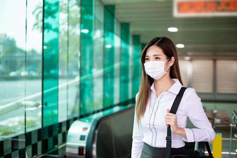 Asian woman with surgical face mask protection - she commutes in the metro or train station