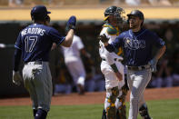Tampa Bay Rays second baseman Brandon Lowe, right, high-fives teammate Austin Meadows (17) after hitting a two-run home run off Oakland Athletics starting pitcher Frankie Montas during the sixth inning of a baseball game Saturday, May 8, 2021, in Oakland, Calif. (AP Photo/Tony Avelar)