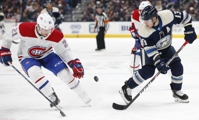 Montreal Canadiens' Nick Cousins, left, and Columbus Blue Jackets' Cam Atkinson chase a loose puck during the second period of an NHL hockey game Tuesday, Nov. 19, 2019, in Columbus, Ohio. (AP Photo/Jay LaPrete)