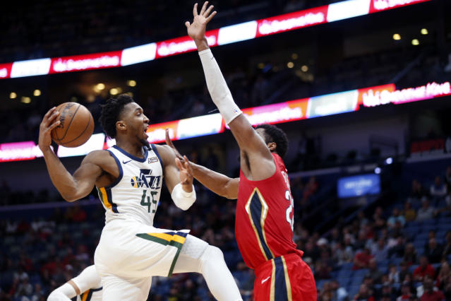 Utah Jazz guard Donovan Mitchell (45) goes to the basket against New Orleans Pelicans forward Derrick Favors during overtime of an NBA basketball game in New Orleans, Thursday, Jan. 16, 2020. The Pelicans won 138-132. (AP Photo/Gerald Herbert)