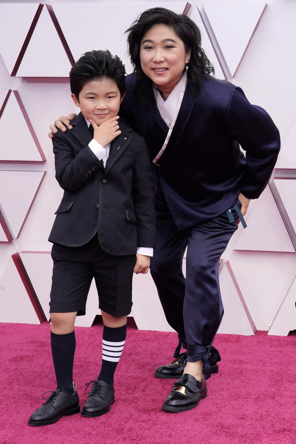 CORRECTS NAME OF WOMAN AT RIGHT TO CHRISTINA OH - Alan S. Kim, left, and Christina Oh arrive at the Oscars on Sunday, April 25, 2021, at Union Station in Los Angeles. (AP Photo/Chris Pizzello, Pool)