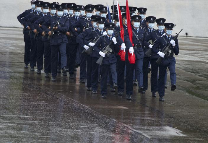 """Hong Kong police show their new goose step marching style on the National Security Education Day at a police school in Hong Kong Thursday, April 15, 2021. Authorities in Hong Kong are marking the day with a police college open house, where police personnel demonstrated the Chinese military's """"goose step"""" march, replacing British-style foot drills. The """"goose step"""" march is one in which troops swing their legs off the ground in unison, keeping each leg straight.(AP Photo/Vincent Yu)"""