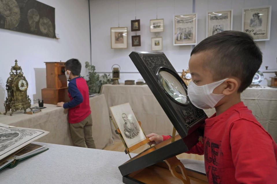 "Visitors wearing face masks to protect against the spread of the coronavirus, play a photo viewer, right, and a stereoscope made from France, at an exhibition ""A Journey to Europe in 1900"", in Hong Kong, Saturday, Feb. 6, 2021. (AP Photo/Kin Cheung)"