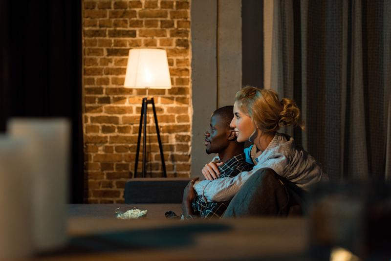 A couple watching TV with a bright lap against a brick wall in the background.