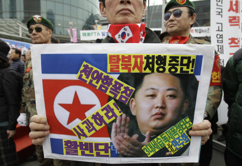 A South Korea's veteran holds a placard showing North Korea's new leader Kim Jong Un and flag during an anti-North Korea protest rally in Seoul, South Korea, Friday, March 16, 2012. North Korea announced Friday it will launch a long-range rocket mounted with a satellite in honor of late President Kim Il Sung's April birthday. (AP Photo/Lee Jin-man)