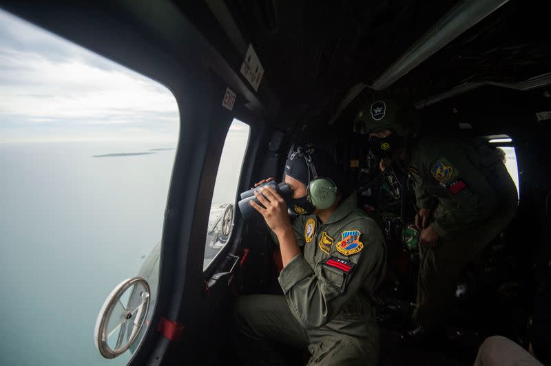An Indonesian Air Force personnel looks through the window of NAS-332 Super Puma helicopter during an aerial search for the Sriwijaya Air SJ-182, which crashed to the sea
