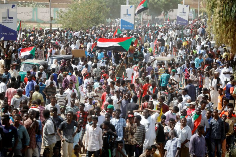 Civilians gather as members of Sudanese pro-democracy protest on the anniversary of a major anti-military protest, as groups loyal to toppled leader Omar al-Bashir plan rival demonstrations in Khartoum
