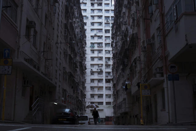 "<p>A man walks in front of a residential and commercial building, center, where the ""coffin home"" are located in Hong Kong. (Photo: Kin Cheung/AP) </p>"