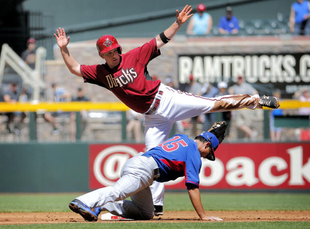 Arizona Diamondbacks' Aaron Hill tries to avoid the tag by Chicago Cubs' Darwin Barney (15) after trying to steal during the first inning of an exhibition spring training baseball game Saturday, March 29, 2014, in Phoenix. Hill was out on the play. (AP Photo/Matt York)