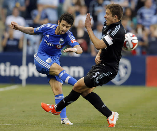 Sporting KC defender Matt Besler (5) blocks a kick by Montreal Impact midfielder Felipe Martins, left, during the first half of an MLS soccer match in Kansas City, Kan., Saturday, April 19, 2014. (AP Photo/Orlin Wagner)