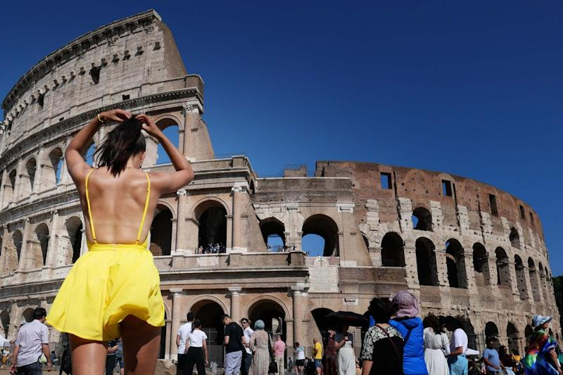A tourist adjusts her hair while walking under the sun in front of the Colosseum in Rome. (AFP/Getty Images)