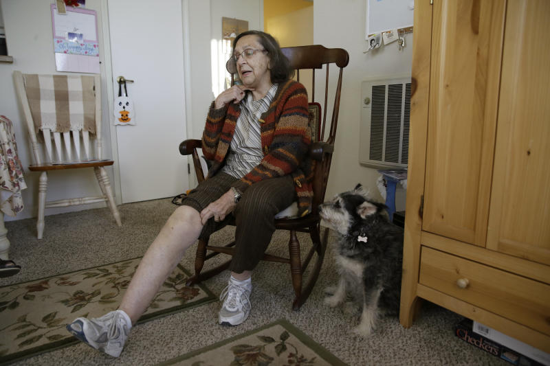 Helen Wagar, who is in her 80s, displays her swollen knee from a fall in a dark stairway during the power blackouts as her dog Pixie looks on at the Villas at Hamilton housing complex for low income seniors Wednesday, Oct. 30, 2019, in Novato, Calif. Wagar fell after stumbling over another woman who had fallen in the stairway. Pacific Gas & Electric officials said they understood the hardships caused by the blackouts but insisted they were necessary. (AP Photo/Eric Risberg)