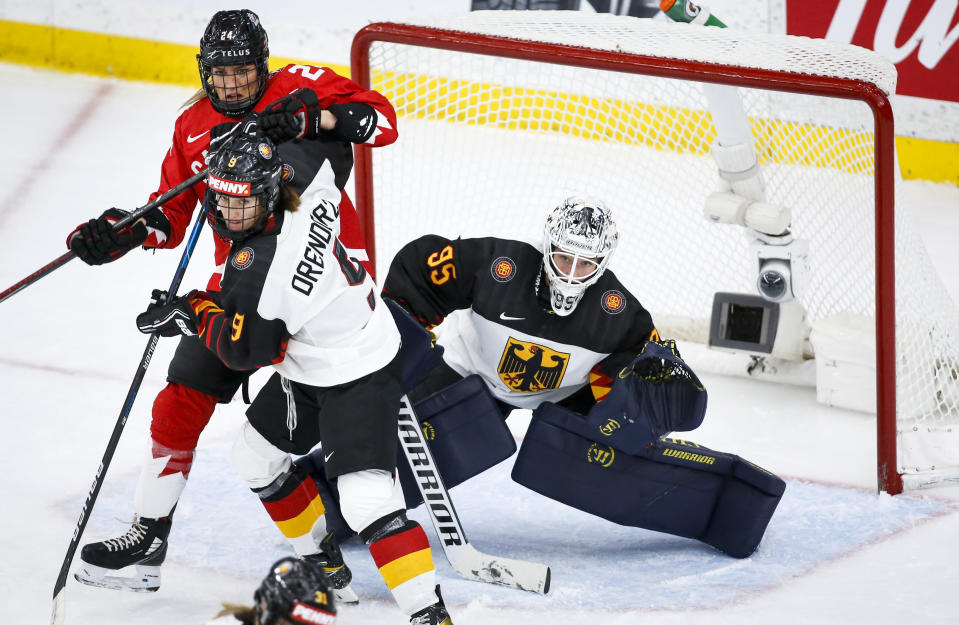 Germany goalie Franziska Albl, right, tries to see past teammate Rebecca Orendorz, center, and Canada's Natalie Spooner during the first period of an IIHF women's hockey championships quarterfinal in Calgary, Alberta, Saturday, Aug. 28, 2021. (Jeff McIntosh/The Canadian Press via AP)