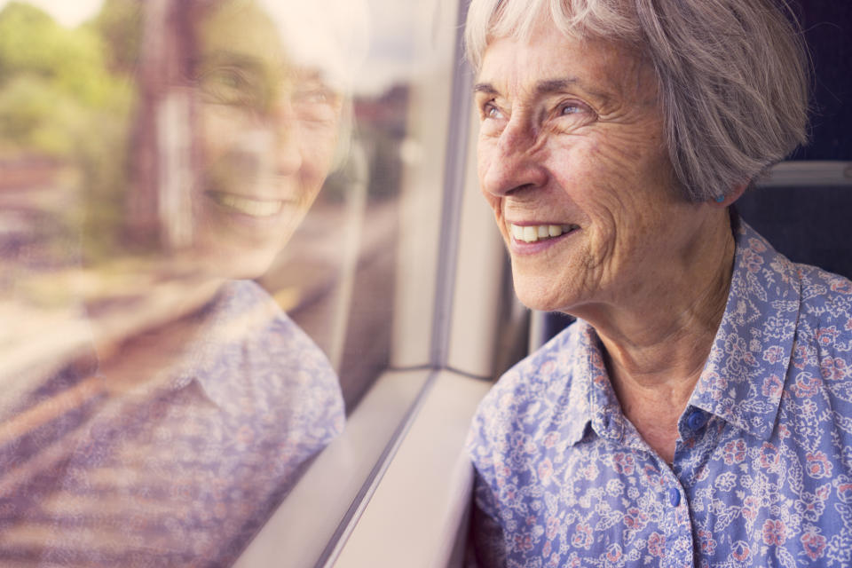 A senior lady happily looking out of a train window.
