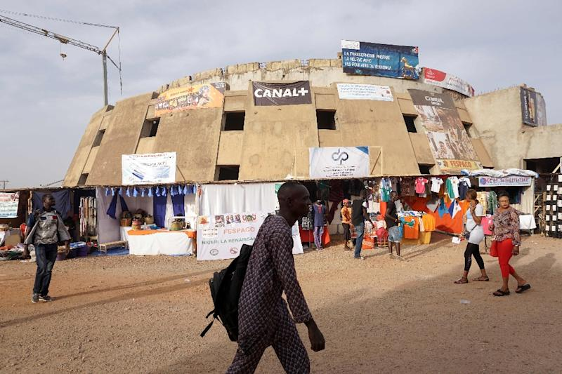 People walk past headquarters of the Africa's top film festival Panafrican Film and Television Festival (Fespaco), on February 28, 2017 in Ouagadougou