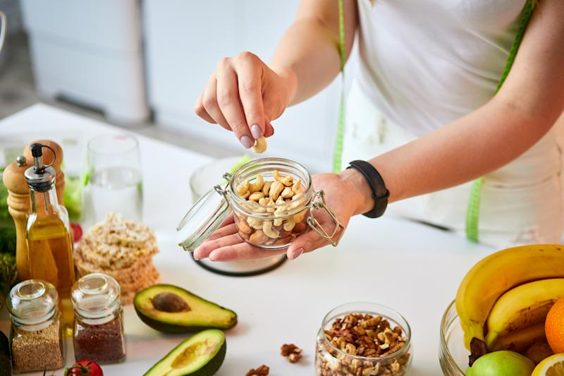 Young happy woman eating different nuts (cashew, hazelnut, almond) in modern kitchen. Healthy food and Dieting concept. Loosing Weight