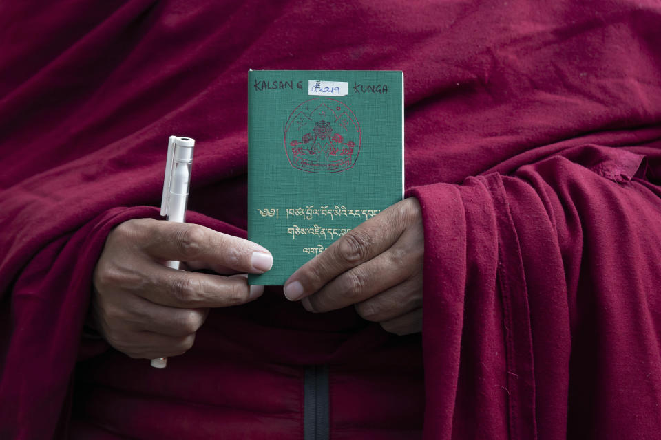 An exile Tibetan Buddhist monk holds his Green Book, which records his tax payments and makes him eligible to vote, as he stands in a queue to vote in Dharmsala, India, Sunday, Jan. 3, 2021. Exile Tibetans Sunday voted in the first round to elect a new political leader and members of the Tibetan parliament in exile. (AP Photo/Ashwini Bhatia)