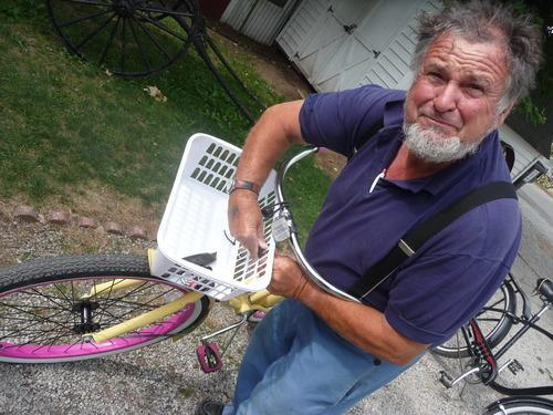 an amish man fixing a bike