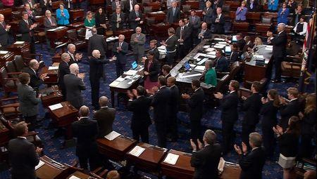 A still image from video shows Senator John McCain, who had been recuperating in Arizona after being diagnosed with brain cancer, acknowledging applause as he arrives on the floor of the Senate after returning to Washington for a vote on healthcare reform, July 25, 2017. SENATE TV/Handout via REUTERS