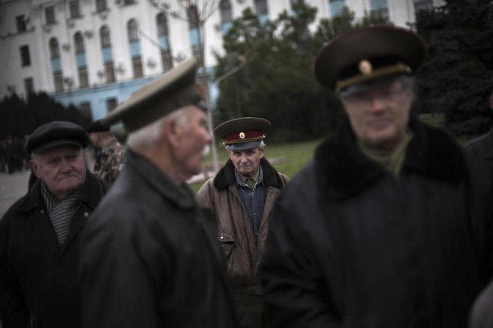 """FILE - In this Saturday, March 8, 2014 file photo, an elderly Ukrainian man stands at Lenin Square with colleagues, all of them dressed in army uniforms from the U.S.S.R., during a pro Russia rally in Simferopol, Ukraine. Despite the pebble beaches and cliff-hung castles that made Crimea famous as a Soviet resort hub, the Black Sea peninsula has long been a corruption-riddled backwater in economic terms. The Kremlin, which decided to take the region from Ukraine after its residents voted in a referendum to join Russia, has begun calculating exactly what it will cost to support Crimea's shambolic economy _ which one Russian minister described as """"no better than Palestine."""" (AP Photo/Manu Brabo, File)"""
