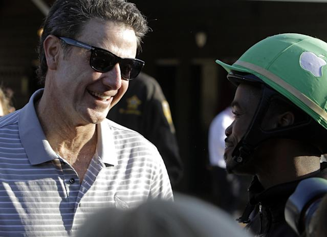Part-owner of Kentucky Derby hopeful Goldencents Rick Pitino, left, talks to jockey Kevin Krigger at Churchill Downs Wednesday, May 1, 2013, in Louisville, Ky. (AP Photo/Garry Jones)