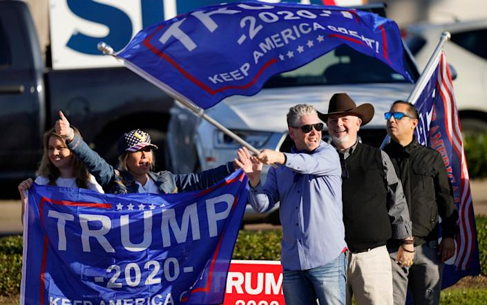 Supporters of President Trump cheer as passing cars honk their horns near a polling location in Houston - AP