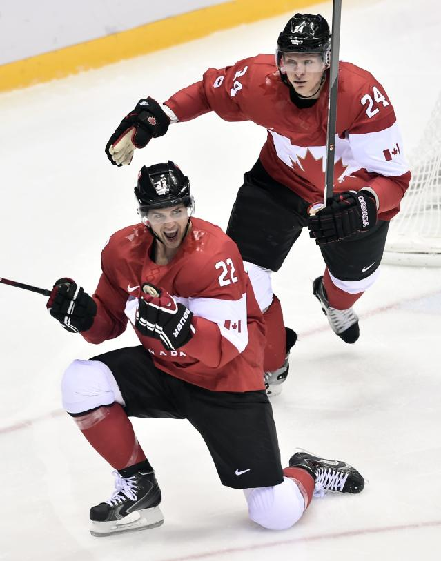 Canada's Jamie Benn (22) celebrates with Jeff Carter (24) ,after scoring the first goal against the United States' during second period hockey semifinal action at the 2014 Sochi Winter Olympics in Sochi, Russia on Friday, Feb. 21, 2014. (AP Photo/The Canadian Press, Nathan Denette)