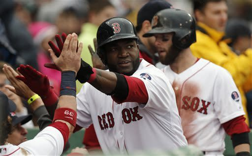 Boston Red Sox's David Ortiz, center, and Dustin Pedroia, right, are greeted at the dugout after they both scored on a single by Daniel Nava during the eighth inning of their 7-4 win over the Cleveland Indians in a baseball game at Fenway Park in Boston, Saturday, May 25, 2013. (AP Photo/Winslow Townson)