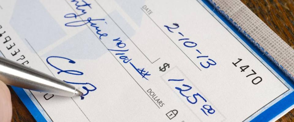 A Check is signed paying bills in ballpoint pen on the desk pay promise