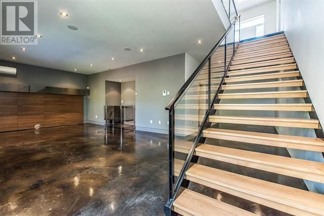 <p><span>7 Palmer Hill Rd., Halifax, N.S.</span><br> Down the custom glass, steel and maple staircase, you'll find a fully finished basement, including media rom and rec room with bar area.<br> (Photo: Zoocasa) </p>
