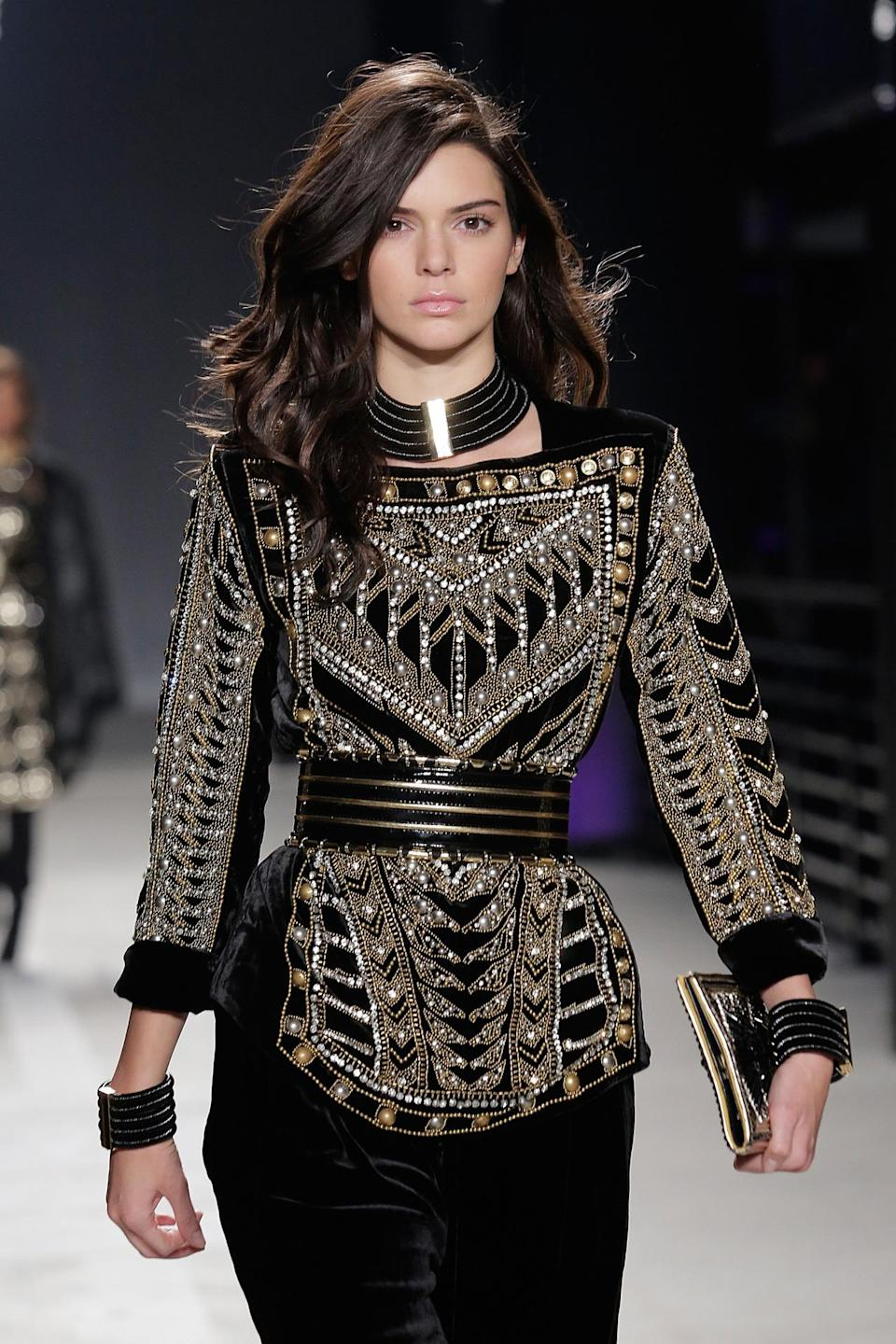 <p>Walking the runway at Balmain x H&M, Jenner looks like a rock 'n' roll legend with voluminous medium-length waves and pink lip gloss. <i>(Photo: Getty Images)</i><br></p>