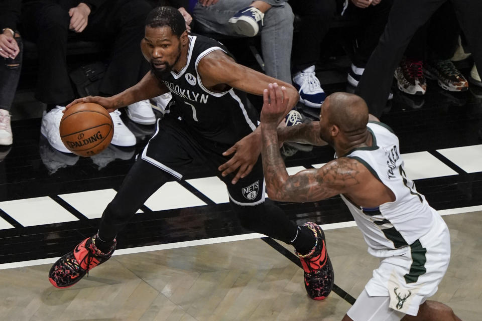 Brooklyn Nets' Kevin Durant, left, drives past Milwaukee Bucks' P.J. Tucker during the first half of Game 7 of a second-round NBA basketball playoff series Saturday, June 19, 2021, in New York. (AP Photo/Frank Franklin II)