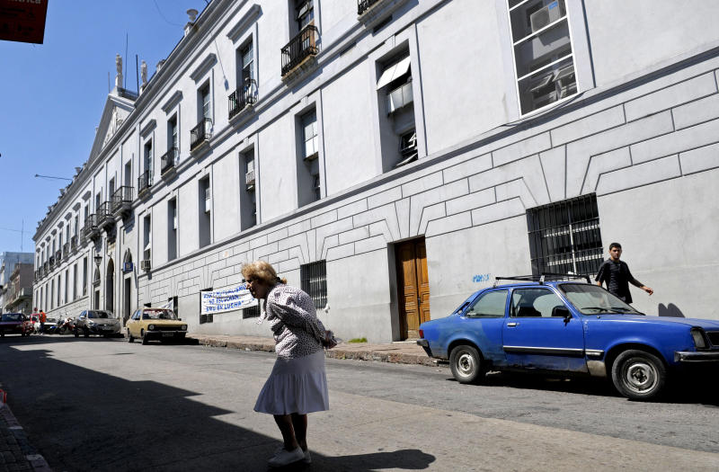 A woman walks by Maciel public hospital in Montevideo, Uruguay, Sunday March 18, 2012. Uruguayan police say an investigation into dozens of possibly induced deaths at two hospitals, including Maciel, has led to the detention of at least two people. Police inspector Jose Luis Roldan said Sunday that officials suspect that hospital workers brought a sort of poison from Brazil and gave it to patients who were in critical condition. (AP Photo/Matilde Campodonico)