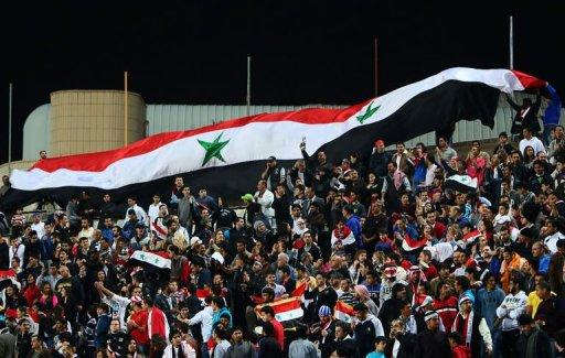 Syrian football fans wave a giant national flag during Syria's final football match against Iraq