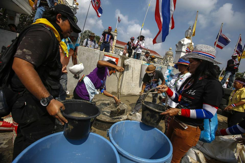 Anti-government protesters mix cement to build a wall to block a gate of the Government House during a rally in Bangkok February 17, 2014. Thousands of protesters seeking to oust Thai Prime Minister Yingluck Shinawatra surrounded the government's headquarters in Bangkok on Monday, in a defiant riposte to police efforts to begin retaking sites they have been occupying for weeks. REUTERS/Athit Perawongmetha(THAILAND - Tags: POLITICS CIVIL UNREST)